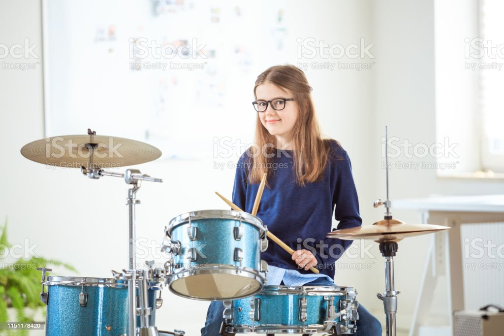 Confident girl playing drums at training class Portrait of confident girl playing drums at training class. Female student is practicing at conservatory. She is casuals at education building. 10-11 Years Stock Photo