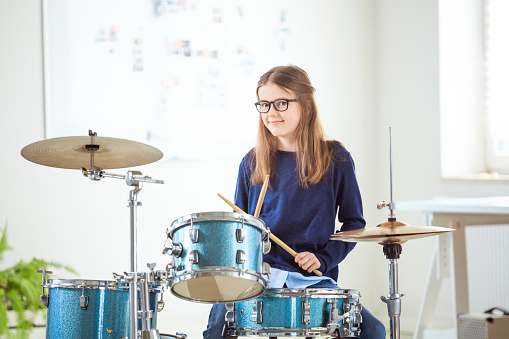 Confident Girl Playing Drums At Training Class Stock Photo - Download Image Now
