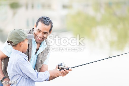istock Confident grandfather fishes with grandson 621099682