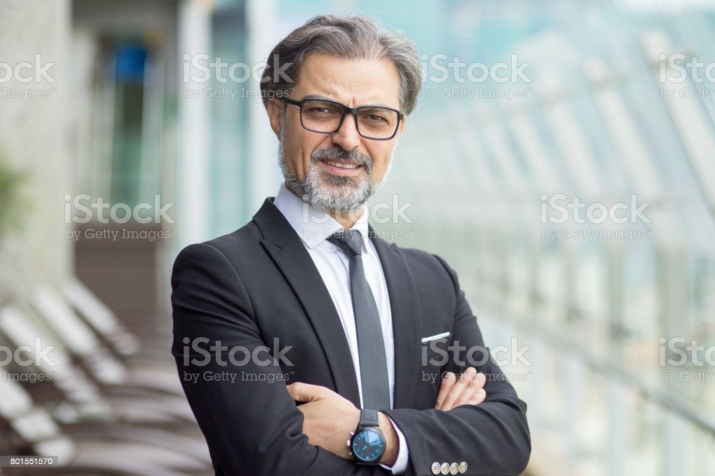 Confident gray-haired senior businessman crossing arms on chest....