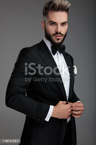 Confident groom unbuttoning his jacket while wearing a black tuxedo and standing on gray studio background