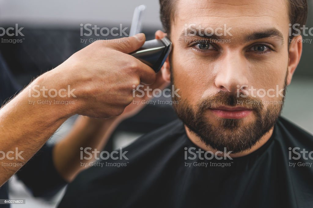 Confident guy sitting at beauty salon stock photo
