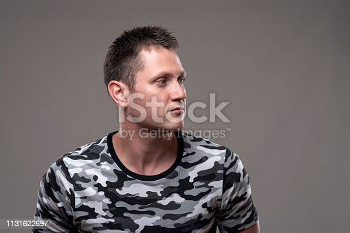 Confident handsome adult young muscular man looking away at copy space