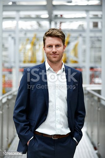 Confident male manager is with hands in pockets at automobile industry. Portrait of smiling businessman standing on elevated walkway. He is wearing businesswear.