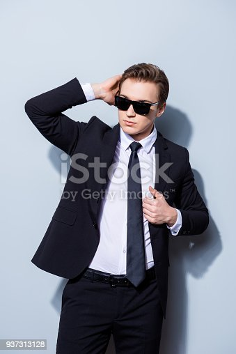 973213156 istock photo Confident handsome young business man is standing on the pure background in sun glasses and suit, fixing his perfect hairstyle. So hot and attractive, harsh and fashionable 937313128