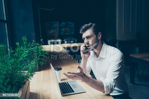 937328186 istock photo Confident handsome young man is having a business conversation,  at work place in a modern coworking, gesturing, well dressed 937306092