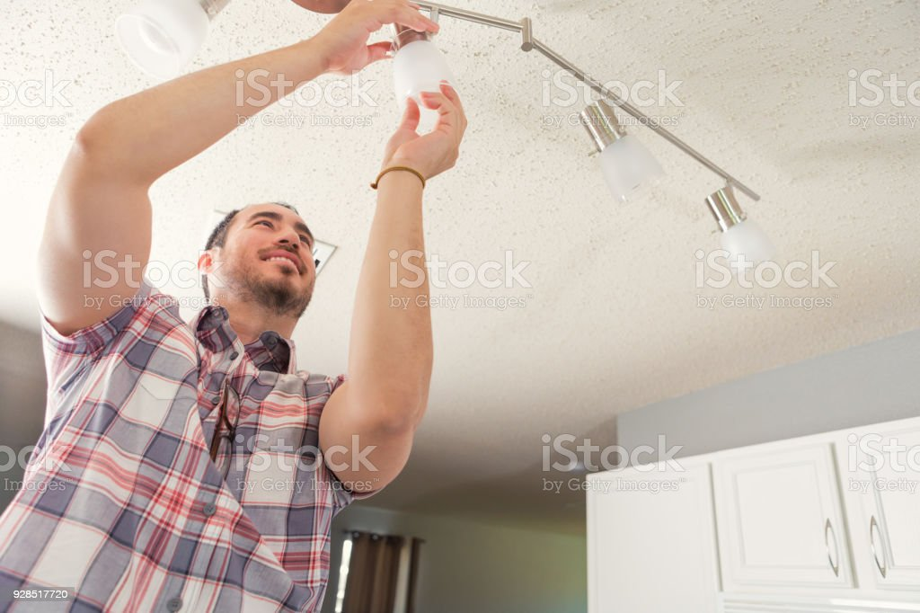 Confident handyman installing lighting in new home stock photo