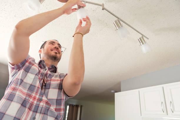 zuversichtlich, handwerker, installation von beleuchtung im neuen zuhause - glühbirne auswechseln stock-fotos und bilder