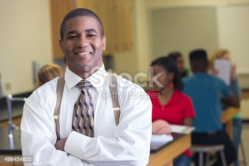 istock Confident high school science teacher standing in classroom with students 499454625