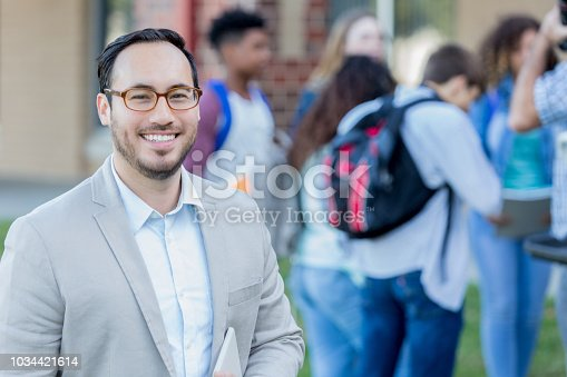 Smiling Hispanic male high school teacher principal stands outside on campus. Students are talking in the background.