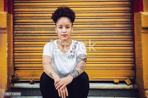 Portrait of woman sitting against closed yellow shutter. Confident female is having tattoo on hands. She is in fashionable casuals.