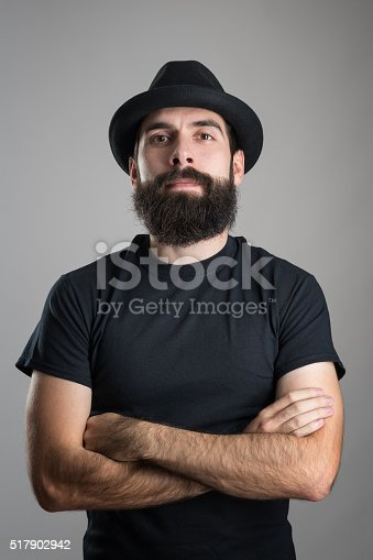 istock Confident hipster with crossed arms wearing black t-shirt and hat 517902942