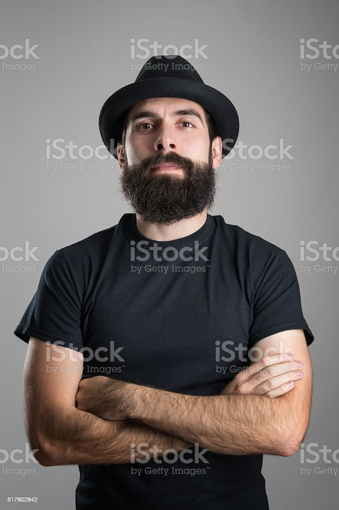 Confident hipster with crossed arms wearing black t-shirt and hat stock photo