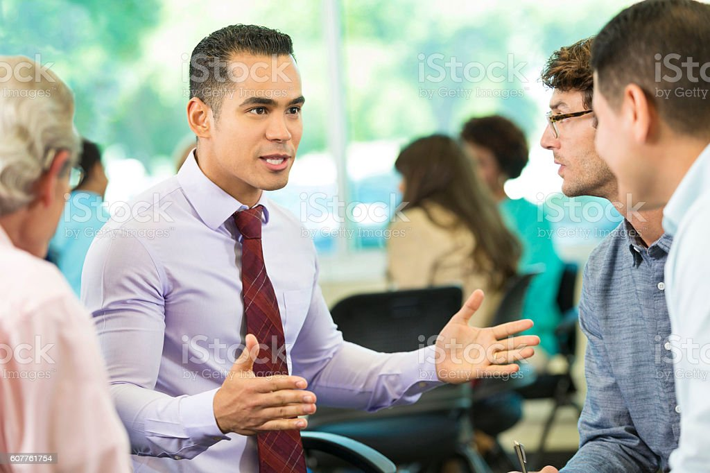 Confident Hispanic man gestures while talking with colleagues stock photo