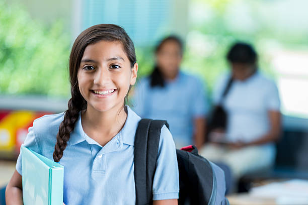 confident hispanic middle schoolgirl before class - uniform stock photos and pictures