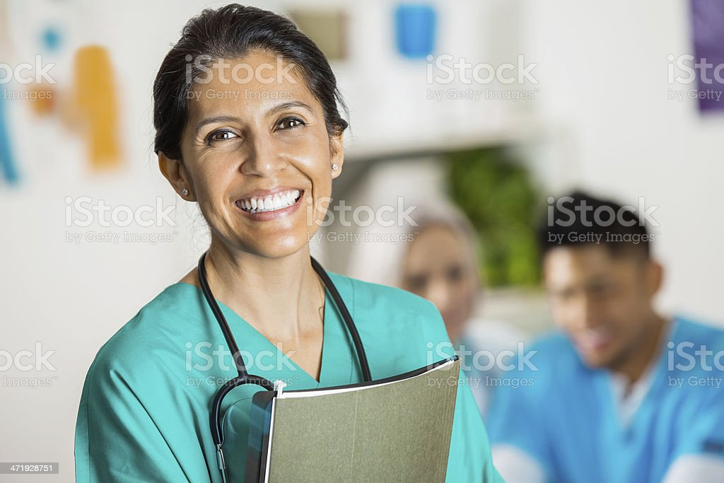 Confident Hispanic nurse or doctor with patient file stock photo