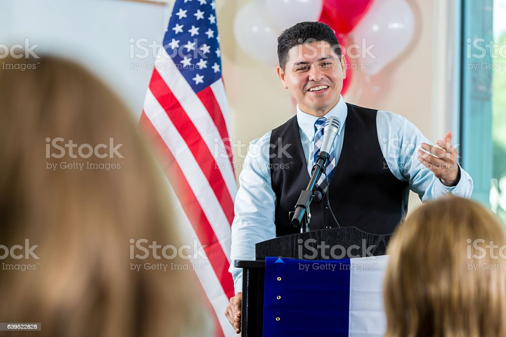 Confident Hispanic politician addresses supporters during rally stock photo