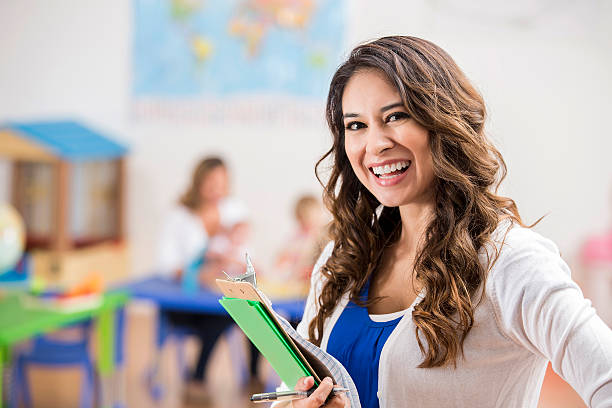 confident hispanic preschool teacher in class - preschool building stock photos and pictures