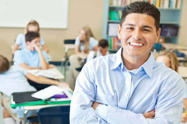 confident hispanic private school teacher in classroom - middle school teacher stock pictures, royalty-free photos & images