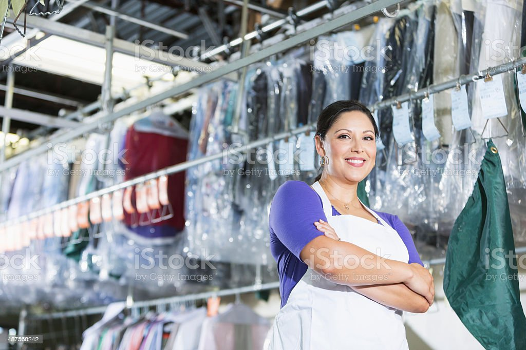Confident Hispanic woman in her dry cleaning store stock photo