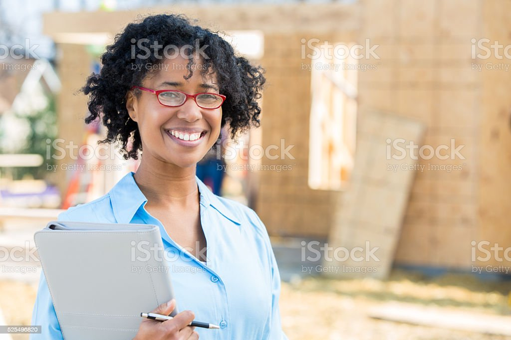 Confident home builder in front of unfinished home stock photo