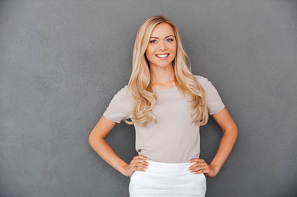 Confident in her abilities. Smiling young blond hair woman holding hands on hips and looking at camera while standing against grey background blond hair stock pictures, royalty-free photos & images