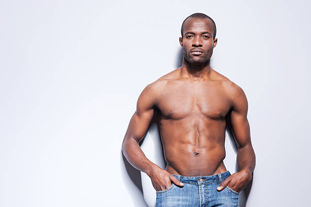 Confident in his perfect body. Handsome young shirtless African man looking at camera and holding hands in pockets while leaning at the grey wall shirtless male models stock pictures, royalty-free photos & images