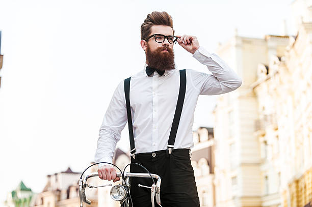 Confident in his perfect style. Low angle view of handsome young man leaning at the bicycle and adjusting eyewear while standing outdoors suspenders stock pictures, royalty-free photos & images