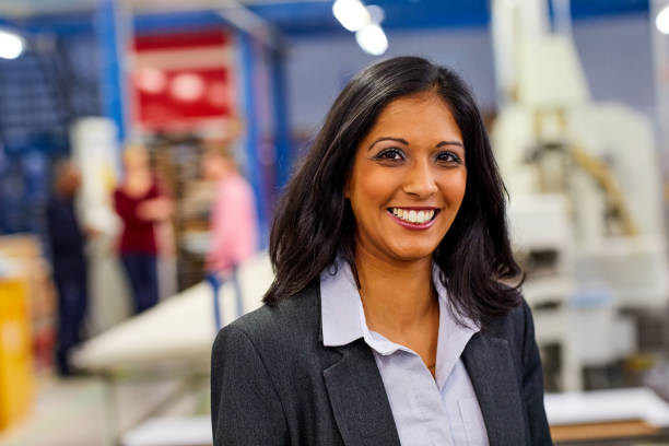 Confident indian businesswoman standing in factory stock photo
