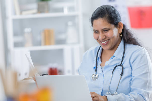 Confident Indian doctor does research in her office stock photo