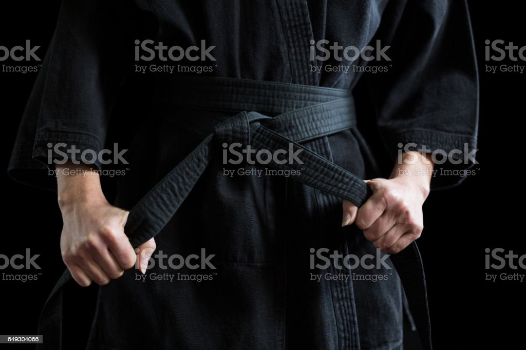 Confident karate player holding his belt stock photo