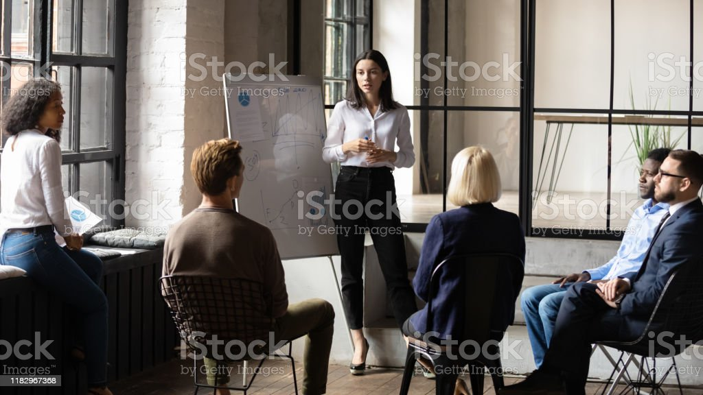 Confident lady business trainer coach give flip chart presentation Confident lady business trainer coach leader give flip chart presentation consulting clients teaching employees training team people speaking explaining strategy at marketing workshop concept Adult Stock Photo