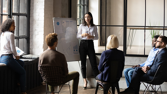 Confident Lady Business Trainer Coach Give Flip Chart Presentation Stock Photo - Download Image Now