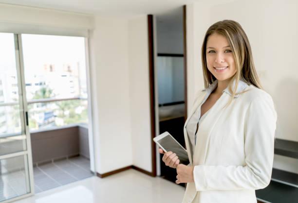 zuversichtlich lateinamerikanischen immobilienmakler in einem hotel blick auf die kamera zu lächeln - immobilienmakler stock-fotos und bilder