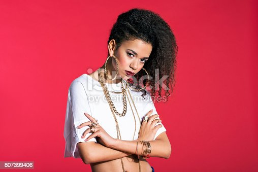 807419930istockphoto Confident latin young woman in hip-hop style against red background 807399406