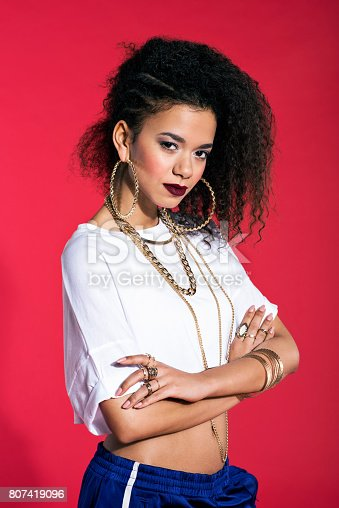 807419930istockphoto Confident latin young woman in hip-hop style against red background 807419096