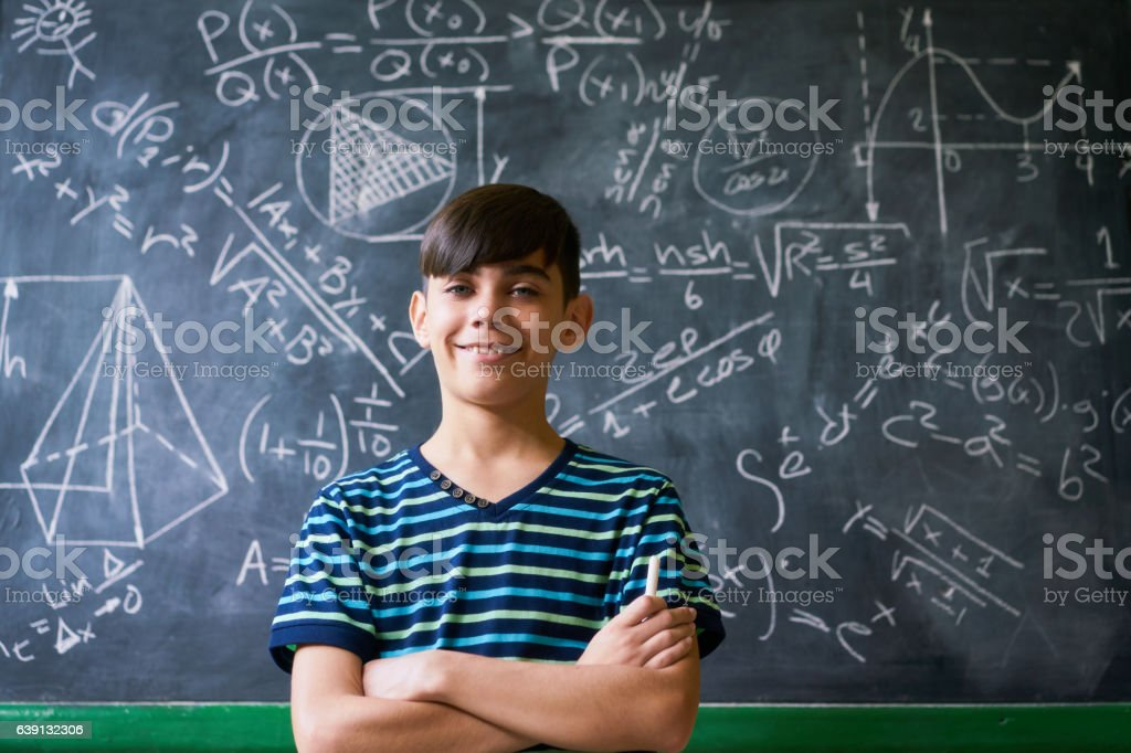 Confident Latino Boy Smiling At Camera During Math Lesson stock photo
