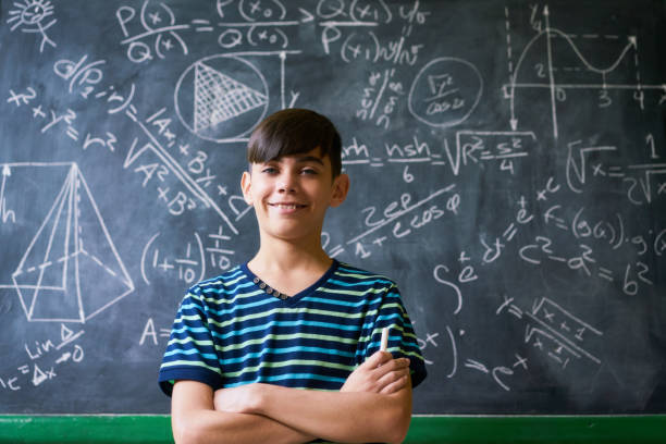 Confident Latino Boy Smiling At Camera During Math Lesson - foto de acervo
