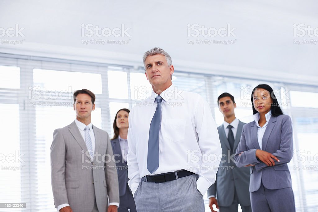 Confident leader standing in front of his team royalty-free stock photo