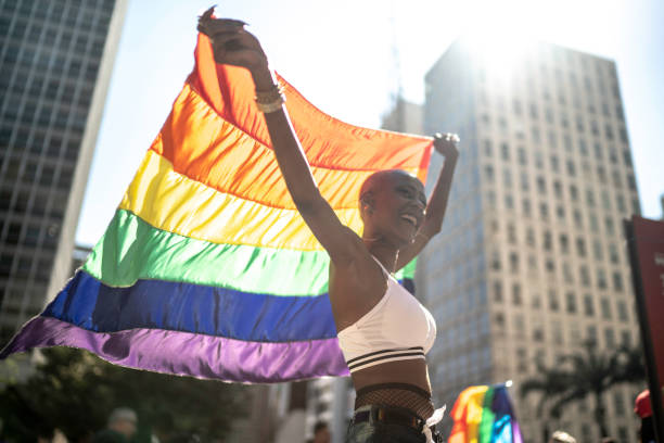 Confident lesbian woman holding rainbow flag during pride parade Confident lesbian woman holding rainbow flag during pride parade gay pride parade stock pictures, royalty-free photos & images