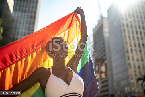 Confident lesbian woman holding rainbow flag during pride parade