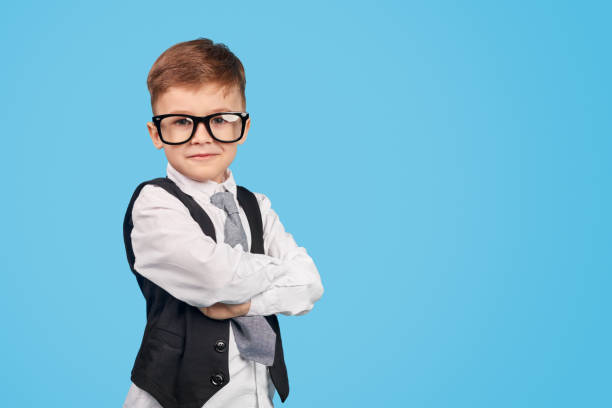 Confident little genius looking at camera Little smart boy in glasses crossing arms and looking at camera while standing near empty space against blue background child prodigy stock pictures, royalty-free photos & images