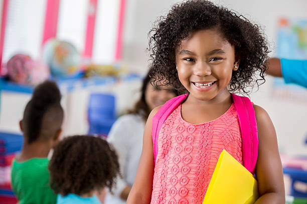Confident little girl in classroom stock photo