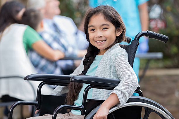 confident little girl in wheelchair at outdoor clinic - sedia a rotelle foto e immagini stock