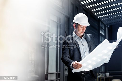 Confident male architect examining blueprint. Mature professional is holding document in office. He is wearing suit.