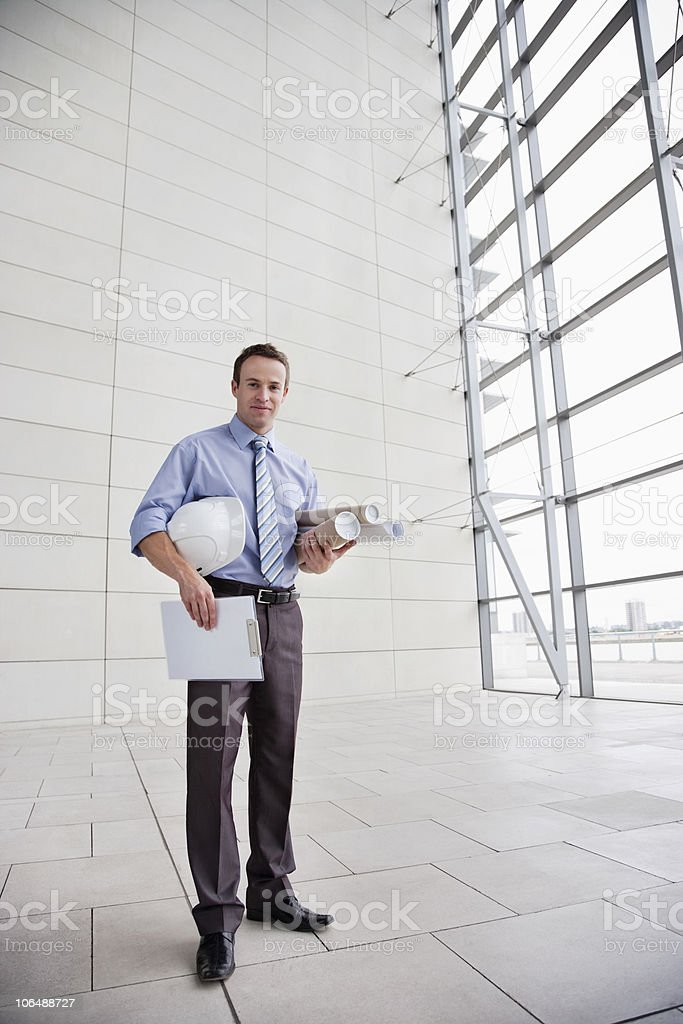 Confident male architect with hardhat and rolled blue prints royalty-free stock photo