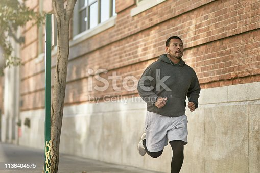 Confident male athlete jogging on sidewalk by wall. Full length of determined young man is exercising in city. He is in sportswear.