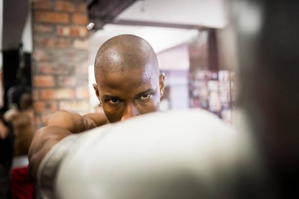 Selbstbewuster männlicher Boxer, der im Fitnessstudio praktiziert – Foto