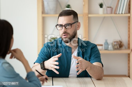 636681940 istock photo Confident male candidate talk at office interview 1227218577