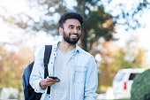 Young adult male colleague student walks on campus. He is carrying a backpack and smartphone.